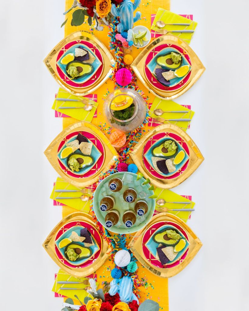Enchanté pink Dinner Plates, Gold To Go Chargers, Buoy Bye Dessert Plates, Enchanté Chartreuse & Pink Guest Napkins arranged on a table with Corona beer bottles and lime slices, Jell-O shots, chips, and guacamole.