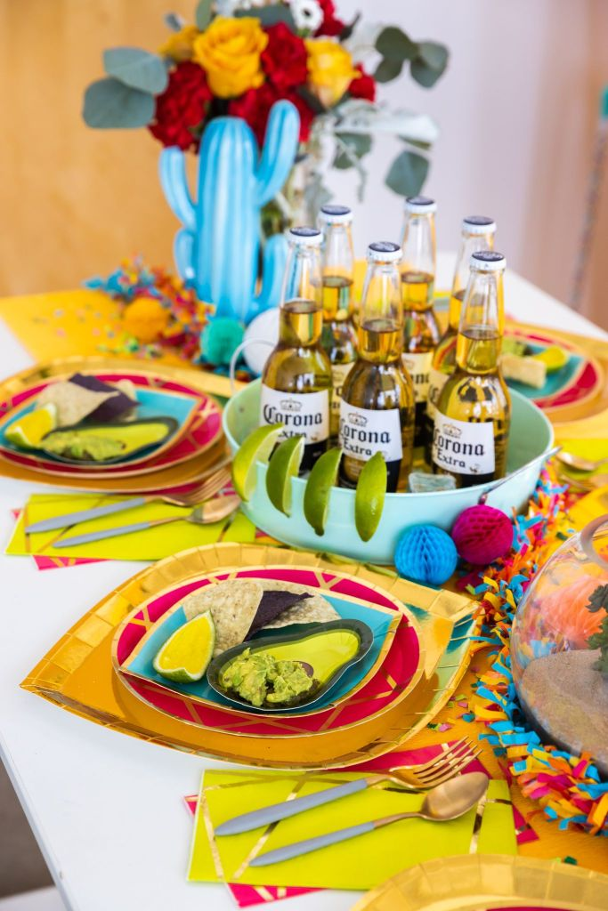Enchanté Pink Dinner Plates, Gold To Go Chargers, Buoy Bye Dessert Plates, Enchanté Chartreuse & Pink Guest Napkins arranged on a table with Corona beer bottles & lime slices, Jell-O shots, chips, and guacamole.